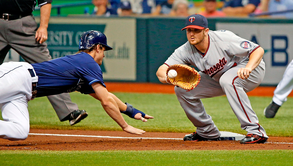 . Twins first baseman Chris Parmelee takes a pickoff throw at first as Tampa Bay\'s Wil Myers dives back to the bag during the first inning.  (Photo by J. Meric/Getty Images)