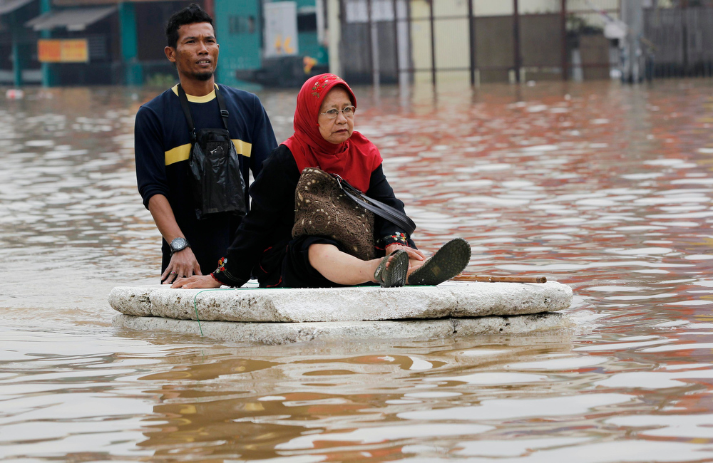 . A woman sits on a makeshift raft as she crosses a flooded road in Jakarta January 16, 2013. Floods inundated several areas of Jakarta due to the overflow of the Ciliwung River and several days of heavy rains in the capital city, local media reported on Wednesday.   REUTERS/Enny Nuraheni