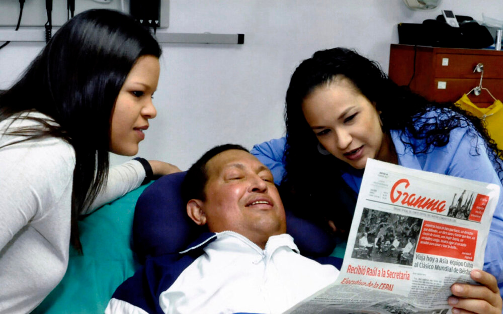 Description of . Venezuela's President Hugo Chavez holds a copy of the newspapers as his daughters, Rosa Virginia (R) and Maria watch while recovering from cancer surgery in Havana in this photograph released by the Ministry of Information on February 15, 2013. Venezuela's government published the first pictures of cancer-stricken Chavez since his operation in Cuba more than two months ago, showing him smiling while lying in bed reading a newspaper, flanked by his two daughters. The 58-year-old socialist leader had not been seen in public since the Dec. 11 surgery, his fourth operation in less than 18 months. The government said the photos were taken in Havana on February 14, 2013.   REUTERS/Ministry of Information/Handout