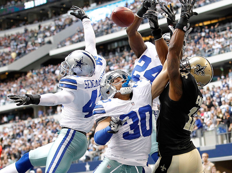 . New Orleans Saints wide receiver Marques Colston (R) is unable to make the catch as he is defended by Dallas Cowboys safety Gerald Sensabaugh (L), corner back Sterling Moore and Morris Claiborne in the first half of their NFL football game in Arlington, Texas December 23, 2012.  REUTERS/Mike Stone