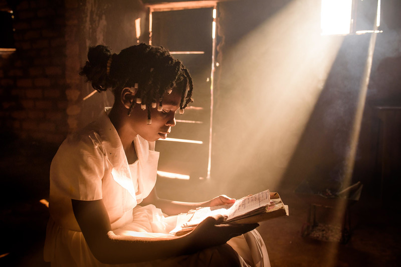 """Kapinga Alphoncine, 13 yr-old girl, reads in English from her old school exercise book.  She lives with her grandmother, Kapinga Godelive, 66 and her 3 brothers: 1-Francois Ngondo, 14 2-Mbuyamba Phillip, 9 3-Beya Honore, 6 Kananga, DRC Democratic Republic of Congo.  School Kapinga doesn't attend school right now. She used to but had to stop when her father died because they don't have the money for school fees. She was in grade 7 which is the first grade of high school in the DRC.  She liked school and especially learning English and French.  She still reads her old exercise books. She and her brothers sometimes write on a piece of wood with charcoal. They teach each other.  Kapinga's grandmother would be happy to have her go back to school if they could afford it. Quote: """"Taking into account how Kapinga helps, I'd like her to go back to school.  I work hard in the fields and earn a little money to buy flour but not enough to buy food and pay school fees.   Inside Kapinga's four-room house the walls are paint splattered. There is little furniture except for two small tables and an old cabinet. On top sits a dusty old television. A peek behind reveals that it has no cord. Kapinga sits on a low, wooden bench against one wall reading an old school exercise book of English lessons. """"Good morning my friends, good morning.""""  Her English is good in spite of a mispronunciation here and there. High up on the wall to the right is a crucifix. It's as battle worn as the rest of the house. Light streams in through the numerous holes in the tin-sheeted roof. In the yard outside, the house is ringed on all sides with gardens of potato and cassava leaves, sorrel and sugarcane among other things.  In one corner of the yard a few visitors gather on homemade chairs under a thatched-roof patio. Across the compound the afternoon sun throws light on the smaller of the two buildings there. In chalk, just below the roof line are the words, """"Il n'ya pas de rose sans epines."""" There is no ros"""