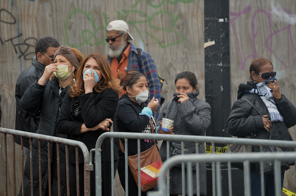 . Bystanders cover their faces against the smoke as they watch the scene of an explosion and building collapse at Park Avenue and East 116th Street March 12, 2014 in the Harlem section of New York.   AFP PHOTO/Stan HONDA/AFP/Getty Images
