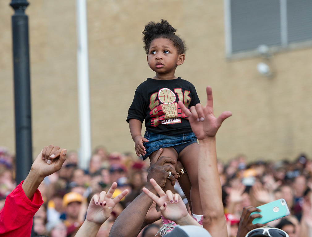 . Layla Oliver 2, of Akron, Ohio, gets an elevated view of the LeBron James homecoming celebration in Akron, Thursday, June 23, 2016. The James-led Cleveland Cavaliers won the NBA basketball championship. (AP Photo/Phil Long)