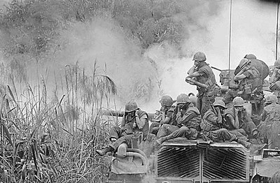 Marines riding atop an M-48 tank, covering their ears, April 3, 1968.