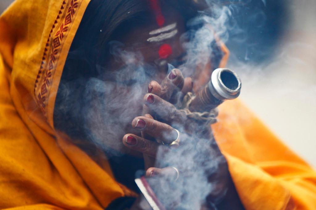 ". A Hindu holy woman smokes marijuana during the \""Shivaratri\"" festival at the courtyard of the Pashupatinath Hindu temple in Katmandu, Nepal, Thursday, Feb. 27, 2014.  (AP Photo/Niranjan Shrestha)"