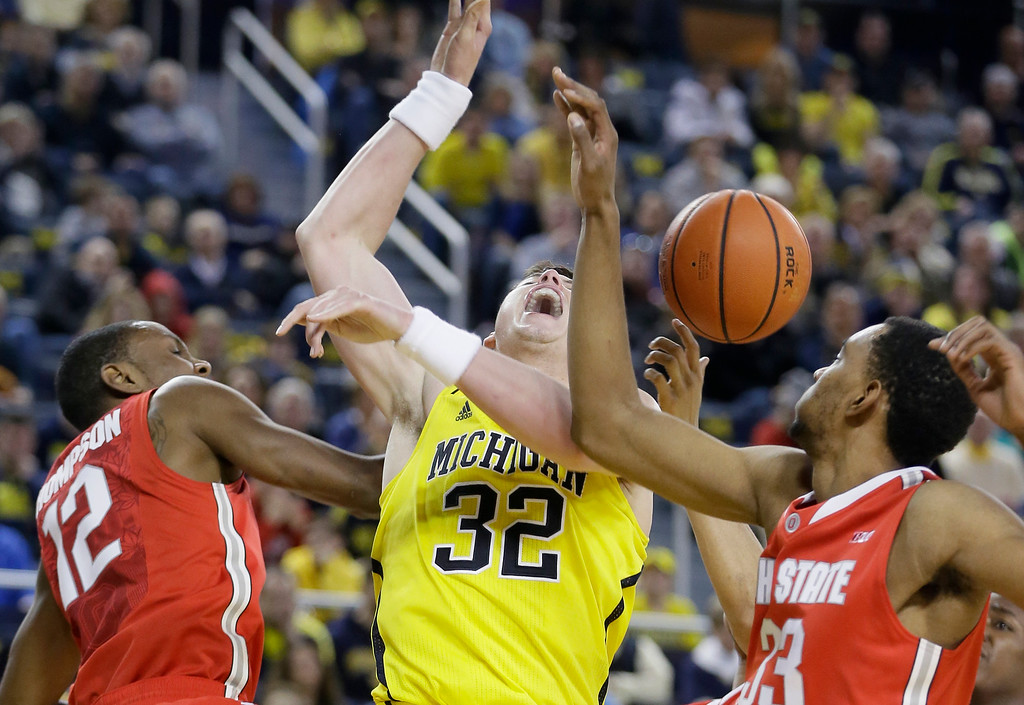. Michigan forward Ricky Doyle (32) loses control of the ball while defended by Ohio State forward Sam Thompson (12) and forward Keita Bates-Diop (33) during the first half of an NCAA college basketball game, Sunday, Feb. 22, 2015 in Ann Arbor, Mich.  (AP Photo/Carlos Osorio)