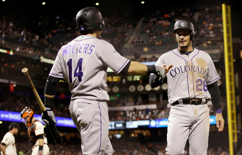 . Colorado Rockies\' Nolan Arenado (28) is greeted by Tony Wolters (14) after Arenado scored on a double from Mark Reynolds during the fifth inning of a baseball game Thursday, May 5, 2016, in San Francisco. (AP Photo/Marcio Jose Sanchez)