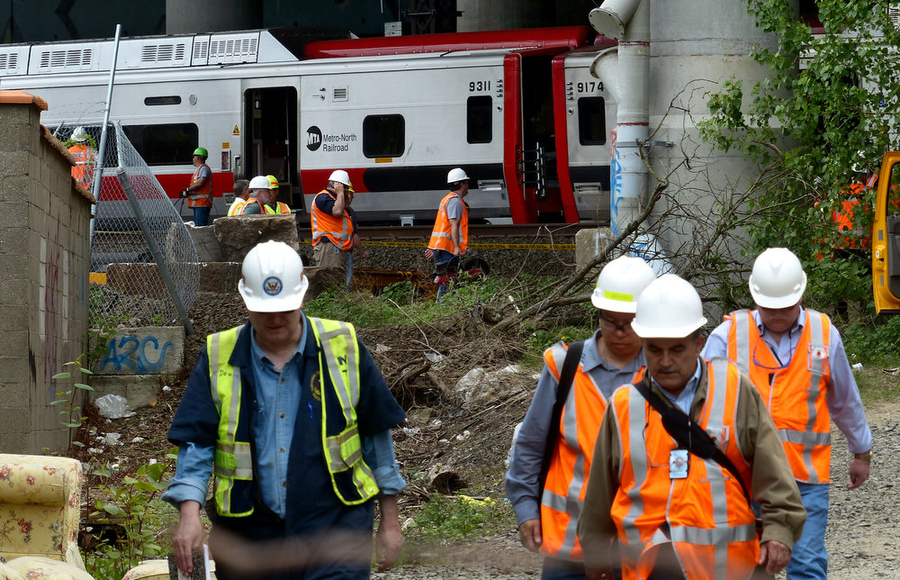 . Metro-North Railroad officials tour the scene of the train derailment, Saturday, May 18, 2013 in Bridgeport, Conn. Officials described a devastating scene of shattered cars and other damage where two trains packed with rush-hour commuters collided in Connecticut, saying Saturday it\'s fortunate that no one was killed and that there weren\'t even more injuries. (AP Photo/The Connecticut Post, Christian Abraham)