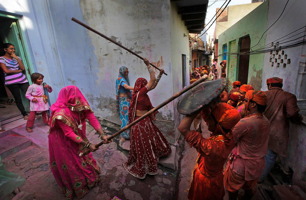 . Indian woman from the village of Barsana hit villagers from Nandgaon with wooden sticks during the Lathmar Holy festival, the legendary hometown of Radha, consort of Hindu God Krishna, in Barsana, 115 kilometers (71 miles) from New Delhi, India, Thursday, March 21, 2013. During Lathmar Holi the women of Barsana beat the men from Nandgaon, the hometown of Krishna, with wooden sticks in response to their teasing as they depart the town. (AP Photo/Manish Swarup)