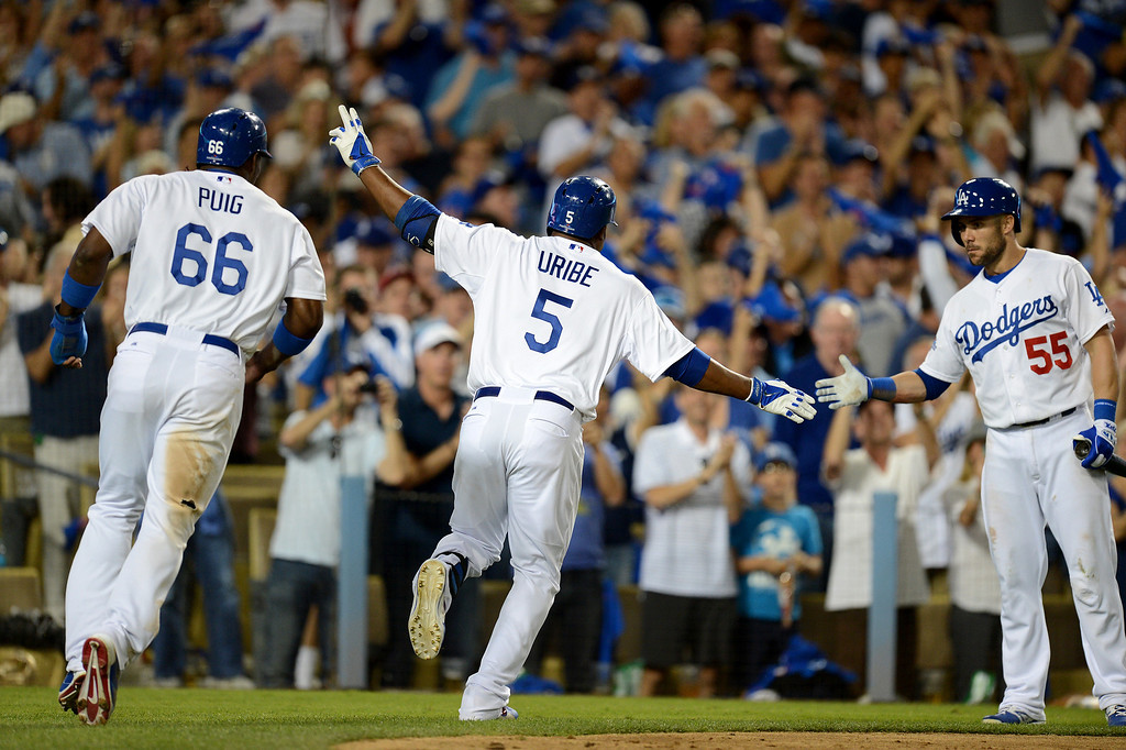 . Los Angeles Dodgers\' Juan Uribe brings in a two-run home run with Yasiel Puig in the fourth during game 3 of the NLDS at Dodger Stadium Sunday, October 6, 2013. (Photo by Hans Gutknecht/Los Angeles Daily News)