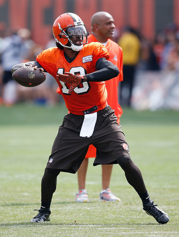 . Cleveland Browns quarterback Robert Griffin III throws near coach Hue Jackson at the NFL football team\'s training camp Tuesday, Aug. 9, 2016, in Berea, Ohio. (AP Photo/Ron Schwane)