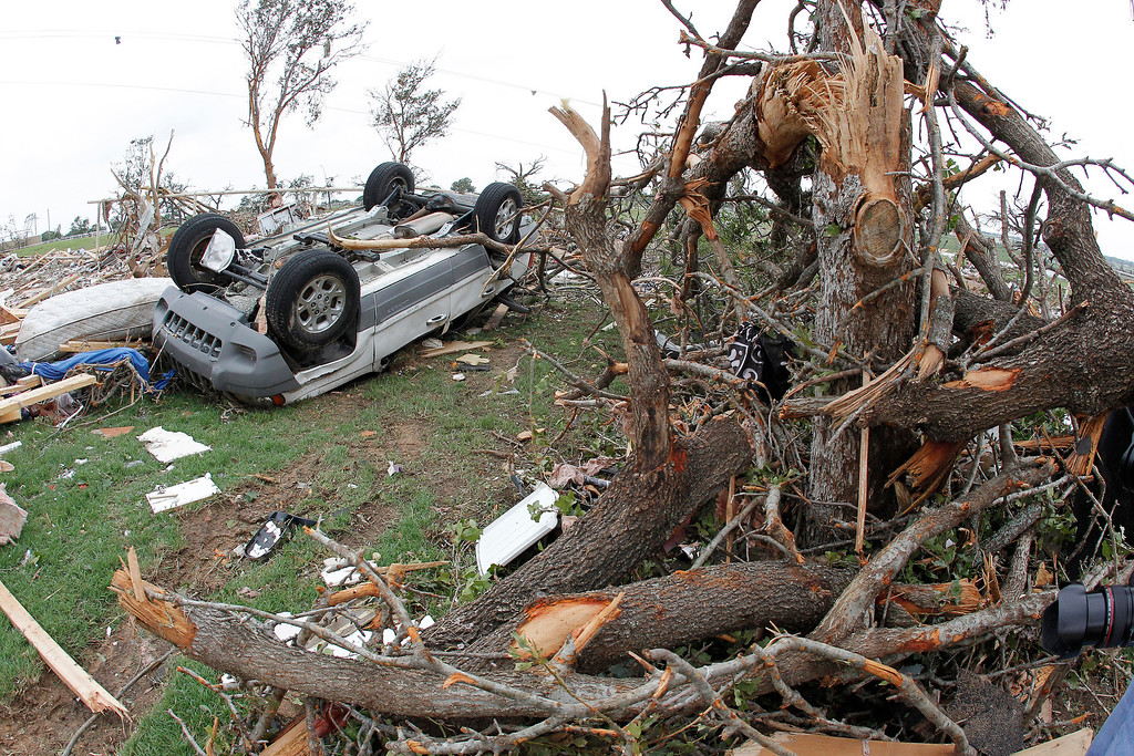 . A toppled car lies next to and crushed trees in the Rancho Brazos neighborhood of Granbury, Texas on Thursday, May 16, 2013.  (AP Photo/The Fort Worth Star-Telegram, Paul Moseley)