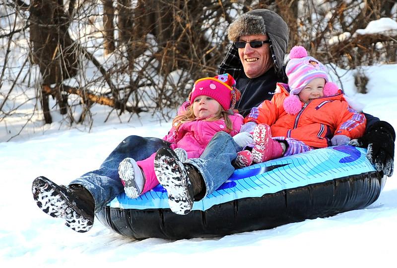 Doug Jackson of Lewiston gives his grandchildren, Ella Jackson, left and Adrianah Pinkham, right,  a ride down the hill at Pettingill Park in Auburn.