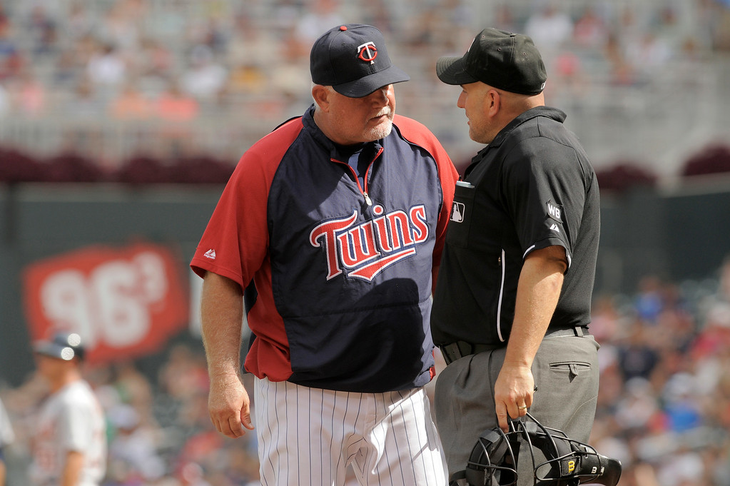 . Minnesota Twins manager Ron Gardenhire, left and home plate umpire Eric Cooper during a baseball game in Minneapolis, Sunday, Aug. 24, 2014. (AP Photo/Tom Olmscheid)