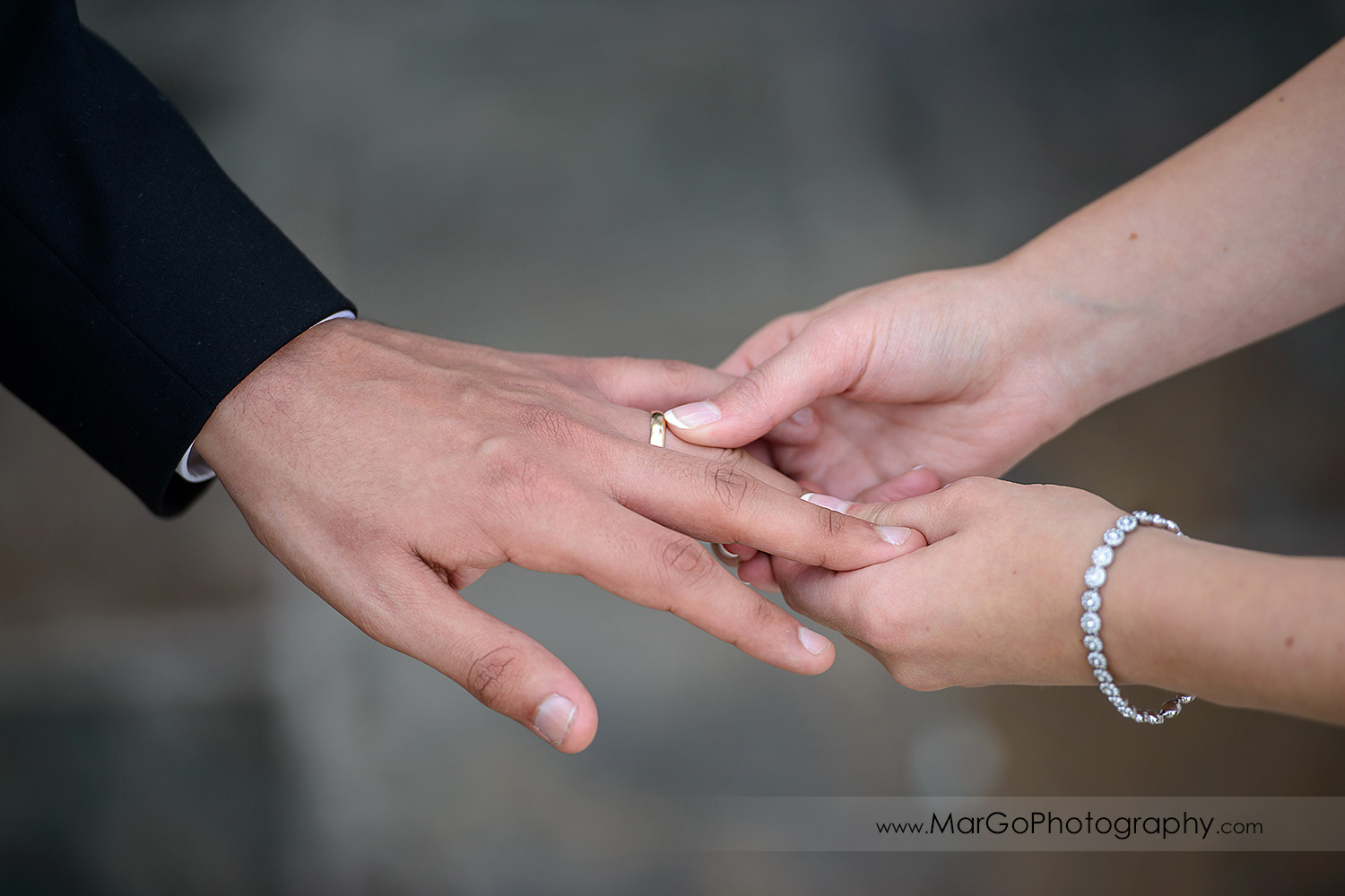 bride putting ring on groom's finger during wedding ceremony at Fremont Century House & Gardens