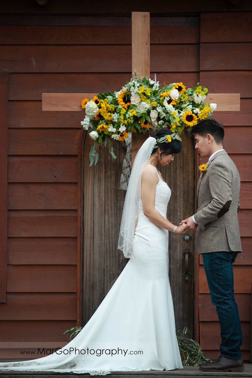 bride and groom holding hands in front of the cross decorated with yellow flowers during wedding ceremony at Long Branch Saloon & Farms in Half Moon Bay