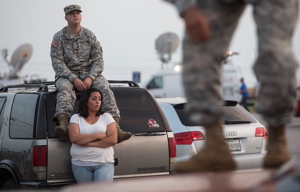 . Lucy Hamlin and her husband, Spc. Timothy Hamlin, wait for permission to re-enter the Fort Hood military base, where they live, following a shooting on base on Wednesday, April 2, 2014, in Fort Hood, Texas. One person was killed and 14 injured in the shooting, and officials at the base said the shooter is believed to be dead. The details about the number of people hurt came from two U.S. officials who spoke on condition of anonymity because they were not authorized to discuss the information by name. (AP Photo/ Tamir Kalifa)