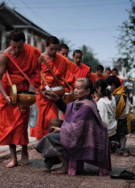 Every morning, hundreds of monks from the various monasteries walk through the streets collecting alms. The atmosphere is solemn and the spiritualism is palpable. The monks walk in single file without uttering a word. They slow down briefly, just enough to lower there bowl in front of the devotes lining the streets. These in turn place a handful of food, usually sticky rice in the bowl. Not as a sigh of charity, but as an act of faith, in the hope that by helping the monks they will be rewarded spiritually.   Luang Prabang, Laos, 2010