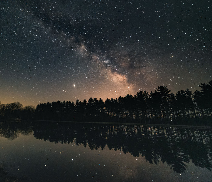 The Milky Way towers over pines reflecting on a lake
