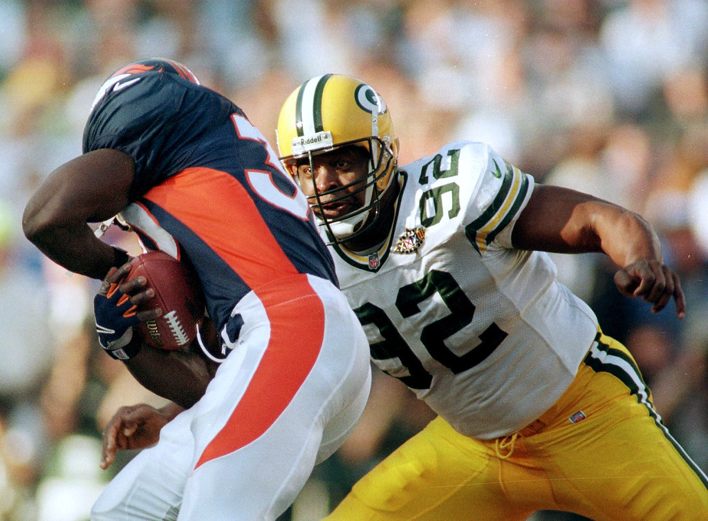 . Denver Broncos Terrell Davis holds on to the ball as  Green Bay Packers Reggie White tries to strip the ball during  Super Bowl XXXII in San Diego CA.  (John Leyba/The Denver Post)