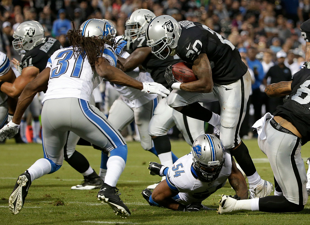 . Oakland Raiders running back Darren McFadden (20) runs against Detroit Lions cornerback Rashean Mathis (31) during the second quarter of an NFL preseason football game in Oakland, Calif., Friday, Aug. 15, 2014. (AP Photo/Marcio Jose Sanchez)