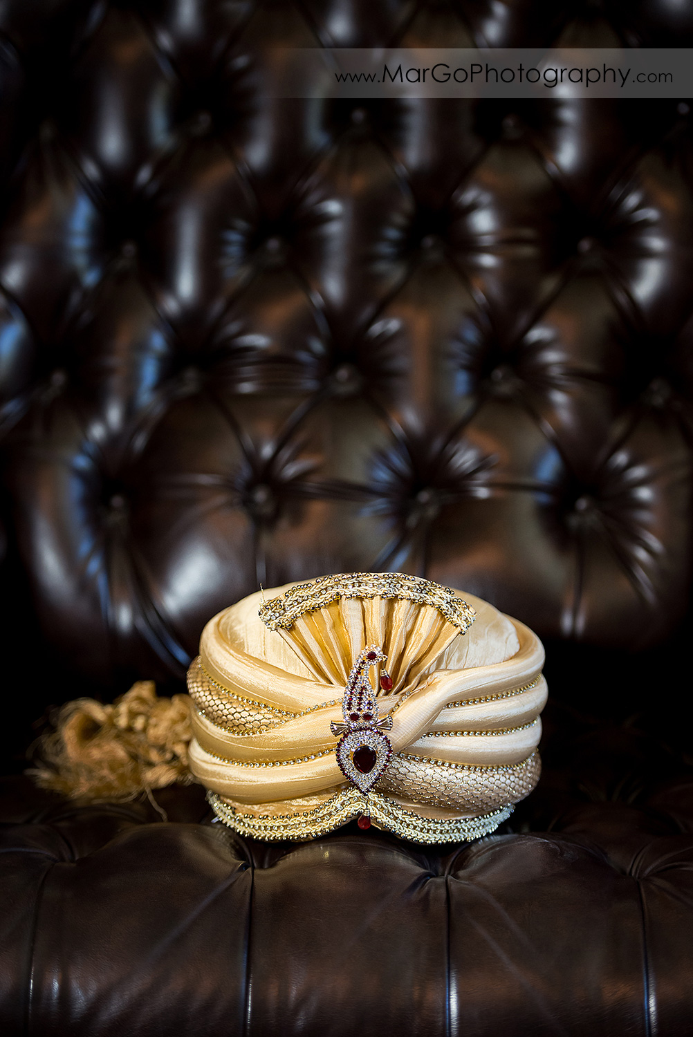 golden wedding headwear for Indian groom on leather chair at Elliston Vineyards in Sunol