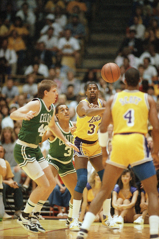 . Earvin ?Magic? Johnson of the Los Angeles Lakers throws the ball down court to teammate Byron Scott, right, as Danny Ainge, left, and Dennis Johnson of the Boston Celtics look on during the NBA finals at the Forum at night on Thursday, June 4, 1987 in Inglewood, California. (AP Photo)