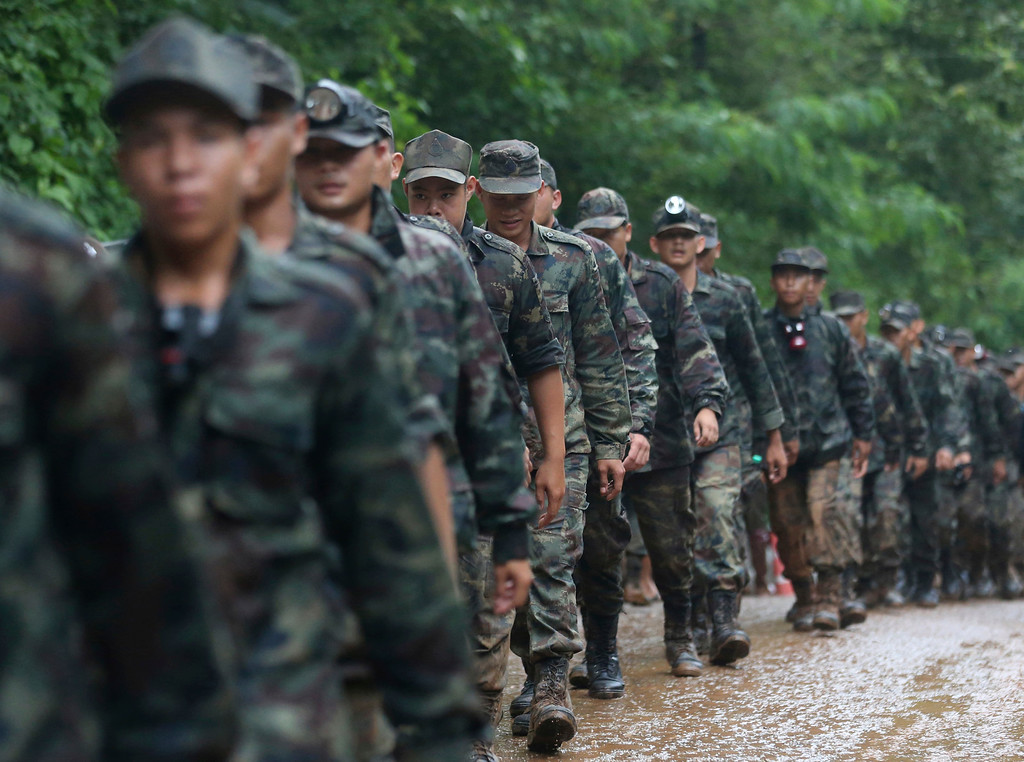 . Thai soldiers march to the cave area where they continue the search for a young soccer team and their coach believed to be missing inside, Wednesday, June 27, 2018, in Mae Sai, Chiang Rai province, northern Thailand. Rain is continuing to fall and water levels keep rising inside a cave in northern Thailand, frustrating the search for 12 boys and their soccer coach who have been missing since Saturday. (AP Photo/Sakchai Lalit)