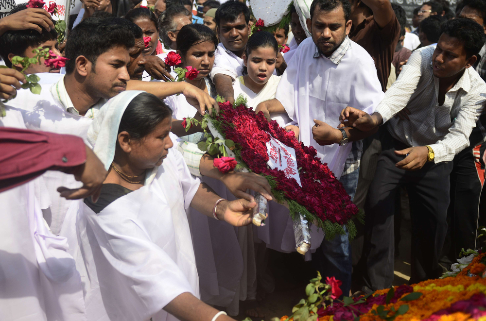 . Bangladeshi activists and relatives of the victims of the Rana Plaza building collapse wear funeral shrouds as they lay a wreath of flowers at an event marking the first anniversary of the disaster at the site where the building once stood in Savar on the outskirts of Dhaka on April 24, 2014. The Rana Plaza building collapsed on April 24, 2013, killing 1138 workers in the world\'s worst garment factory disaster. Western fashion brands faced pressure to increase help for victims as mass protests marked the anniversary. Thousands of people, some wearing funeral shrouds, staged demonstrations at the site of the now-infamous Rana Plaza factory complex.  (MUNIR UZ ZAMAN/AFP/Getty Images)