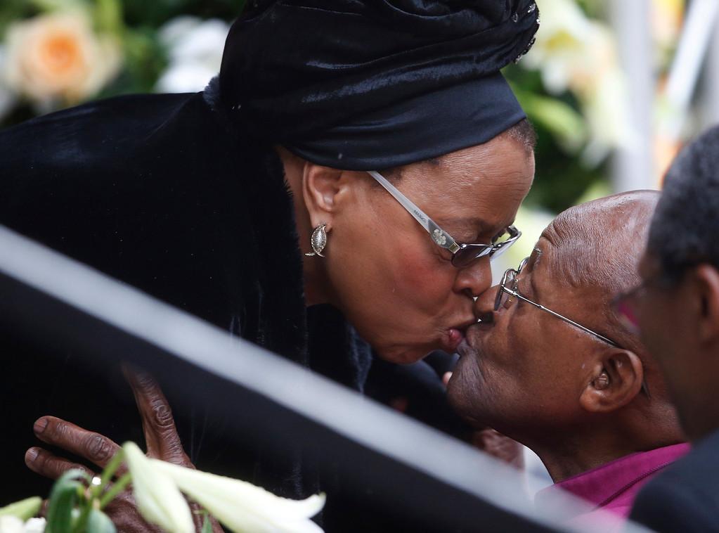 . Graca Machel, widow of Nelson Mandela, kisses Retired Anglican Archbishop Desmond Tutu during the memorial service for former South African president Nelson Mandela at the FNB Stadium in Soweto near Johannesburg, Tuesday, Dec. 10, 2013. (AP Photo/Matt Dunham)
