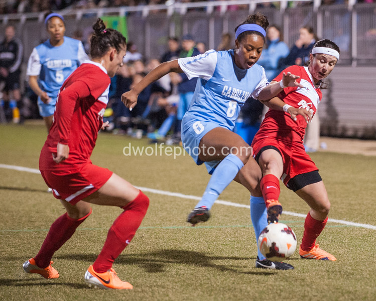 UNC's Amber Munerlyn battles two Spirit players Ali Krieger on the left and Tiffany Weimer on the right for control of the ball.