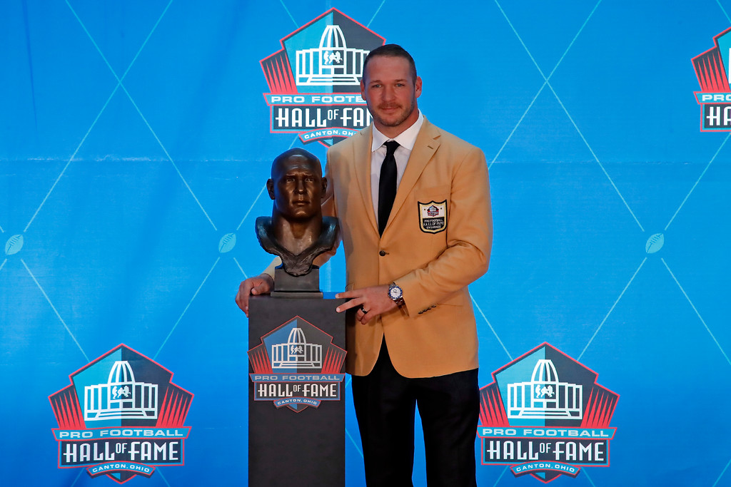 . Former NFL player Brian Urlacher poses with a bust of himself during an induction ceremony at the Pro Football Hall of Fame, Saturday, Aug. 4, 2018 in Canton, Ohio. (AP Photo/Gene J. Puskar)