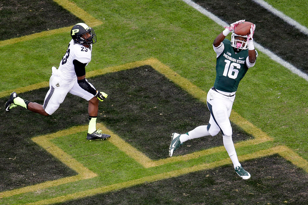 . Michigan State wide receiver Aaron Burbridge (16) pulls in a 13-yard touch down pass in front of Purdue running back Keyante Green (23) in the third quarter of an NCAA college football game in West Lafayette, Ind., Saturday, Oct. 11, 2014. Michigan State won 45-31. (AP Photo/AJ Mast)