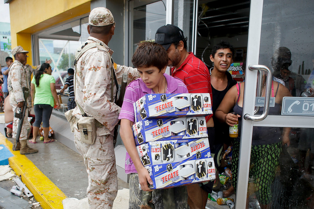 . A young man carries several packs of beer from a convenience store destroyed by Hurricane Odile as Mexican soldiers try to stop people from looting in Los Cabos, Mexico,  Monday, Sept. 15, 2014.   (AP Photo/Victor R. Caivano)