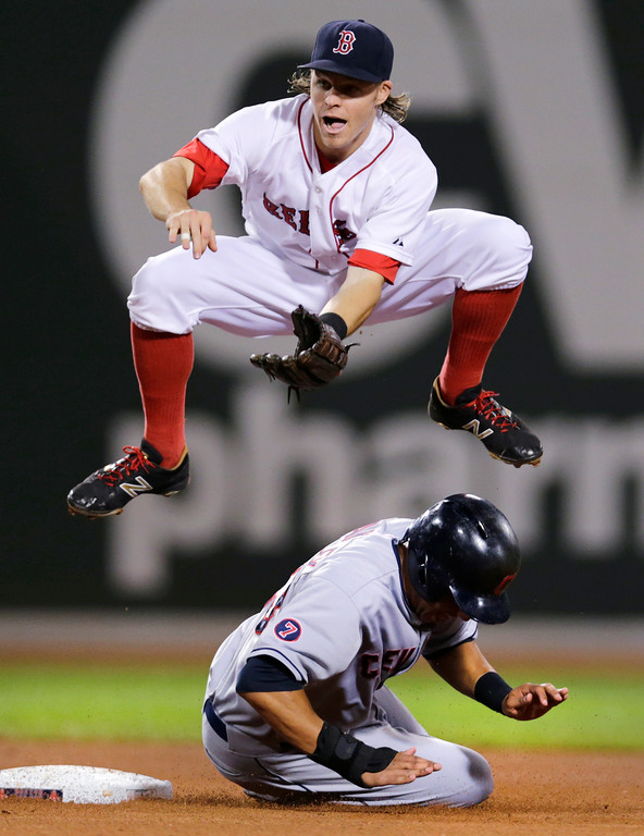 . Boston Red Sox second baseman Brock Holt leaps over Cleveland Indians\' Michael Brantley after making the force out as he turns a double play on a ball hit by Carlos Santana during the fourth inning of a baseball game at Fenway Park in Boston, Wednesday, Aug. 19, 2015. (AP Photo/Charles Krupa)