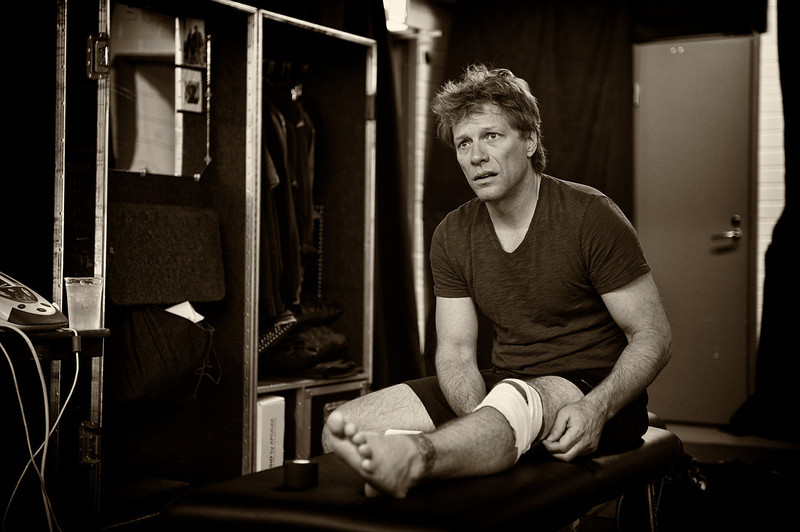 """. June 17, 2011 - Jon Bon Jovi shows a look of concern backstage after tearing the meniscus in his left knee during his band Bon Jovi\'s show at Olympic Stadium in Helsinki, Finland on June 17, 2011. Mr. Bon Jovi was unaware what the injury was at the time, but finished the show and would have surgery to remove the meniscus just over two weeks later.  (Photo credit: David Bergman / Bon Jovi)  \""""Jon Bon Jovi injured his knee during a 2011 show in Helsinki,\"""" remembers Bergman. \""""He had a major tear of his left meniscus and had trouble putting weight on it, but still powered through the rest of the show. Afterwards, he refused crutches and gingerly walked back to the dressing room. Management sent everyone else back to the hotel, except for Jon�s chiropractor / trainer Dean Grillo and me. I was obviously concerned because we didn�t know how bad the injury was at the time. Of course, Jon is a friend and I wanted him to be OK, but I also knew that an injury to one of the biggest rock stars in the world might have historical importance. I went into \'photojournalist\' mode and simply documented everything that was happening. It was eerily quiet in the room as Dean worked on Jon, who was in obvious pain. Jon didn�t cancel any shows and continued to perform for a couple of weeks until having successful surgery in Ireland.\"""""""