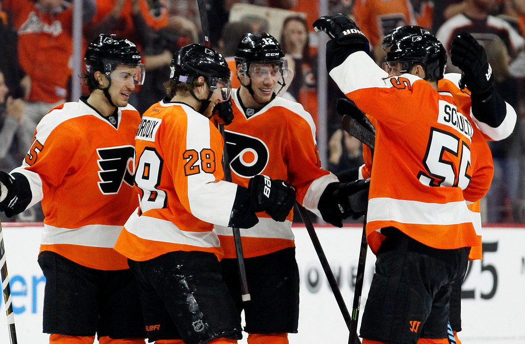 . Philadelphia Flyers\' Michael Raffl (12), center, celebrates his empty-net goal with teammates in the closing minute of the third period of an NHL hockey game against the Detroit Red Wings, Saturday, Oct. 25, 2014, in Philadelphia. The Flyers won 4-2. (AP Photo/Tom Mihalek)