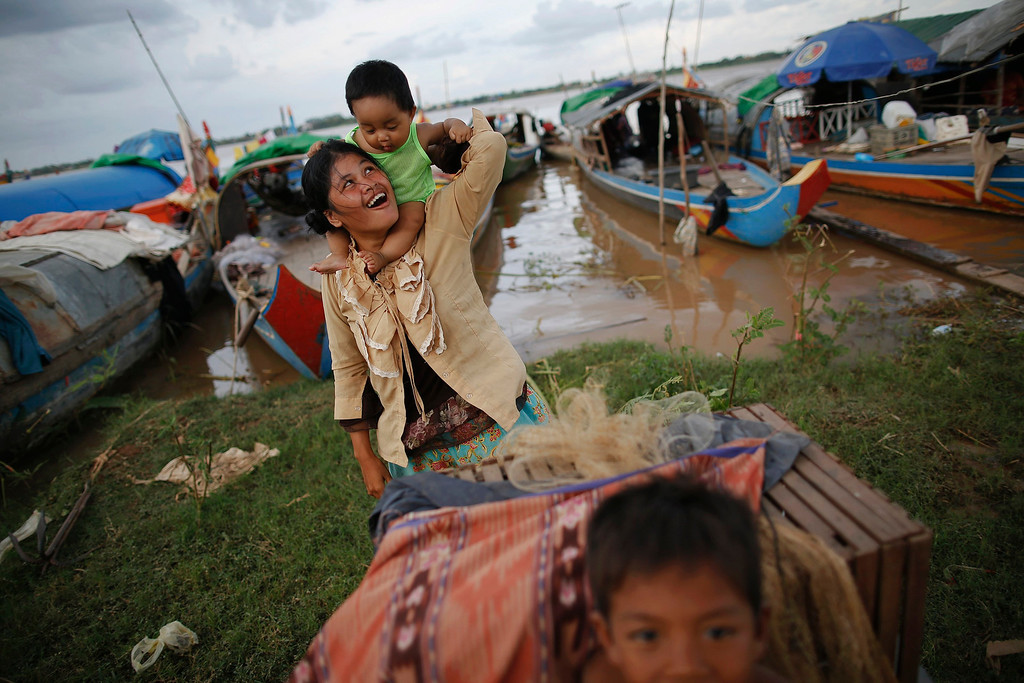 . An ethnic Cham Muslim woman plays with her child on banks of Mekong river in Phnom Penh July 27, 2013. About 100 ethnic Cham families, made up of nomads and fishermen without houses or land who arrived at the Cambodian capital in search of better lives, live on their small boats on a peninsula where the Mekong and Tonle Sap rivers meet, just opposite the city\'s centre. The community has been forced to move several times from their locations in Phnom Penh as the land becomes more valuable. They fear that their current home, just behind a new luxurious hotel under construction at the Chroy Changva district is only temporary and that they would have to move again soon. Picture taken July 27, 2013.   REUTERS/Damir Sagolj