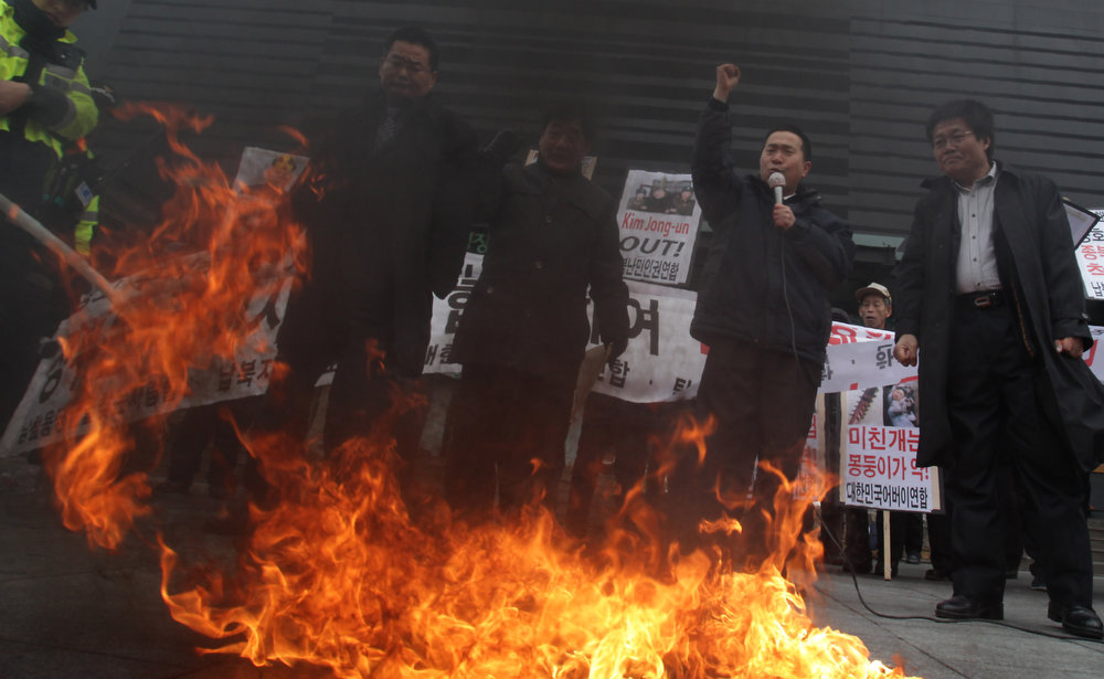 . South Korean conservative protesters burn a flag at an anti-North Korea rally demonstrating against North Korea\'s nuclear test on February 12, 2013 in Seoul, South Korea. North Korea confirmed it had successfully carried out an underground nuclear test, as a shallow earthquake with a magnitude of 4.9 was detected by several international monitoring agencies. South Korea and Japan both assembled an emergency meeting of their respective national security teams after the incident.  (Photo by Chung Sung-Jun/Getty Images)