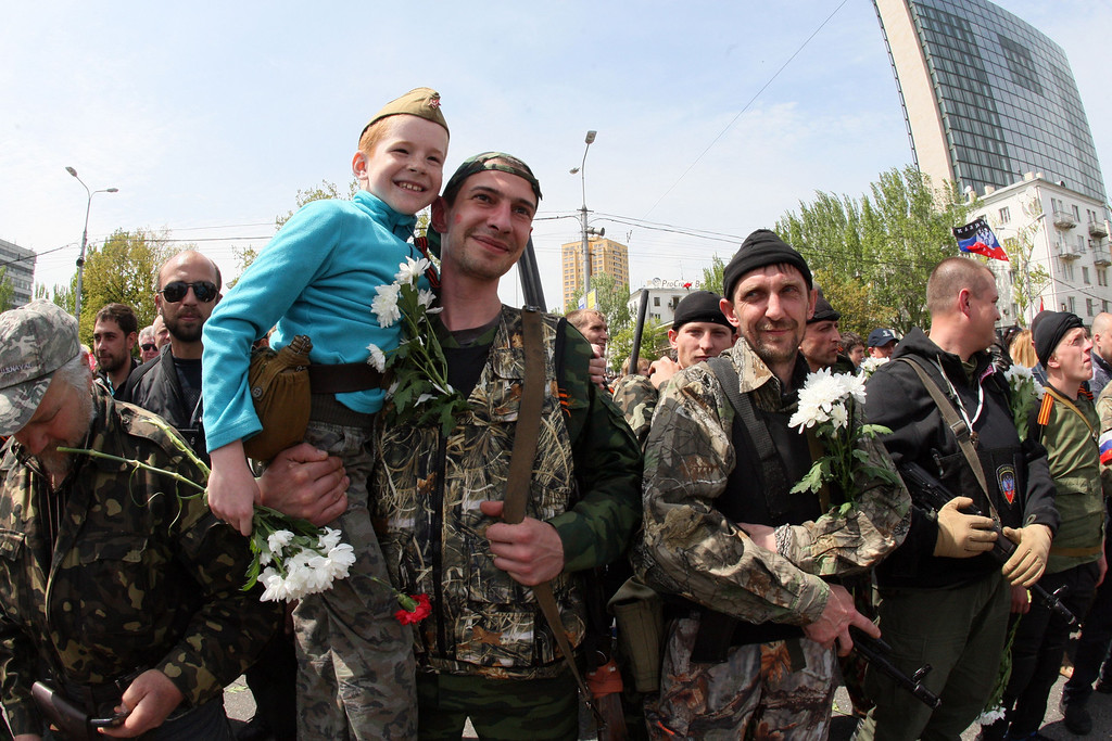 . A pro-Russia militant carries a boy during a rally marking Victory Day in eastern Ukrainian city of Donetsk on May 9, 2014. AFP PHOTO/ ALEXANDER  KHUDOTEPLY/AFP/Getty Images