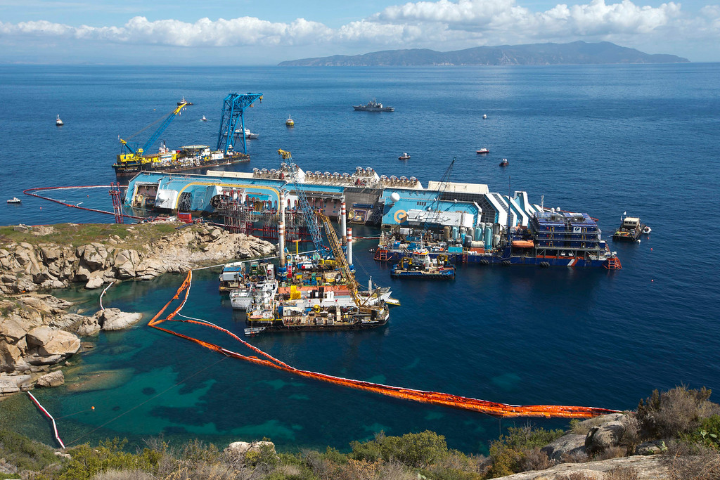 . The Costa Concordia ship lies on its side on the Tuscan Island of Giglio, Italy,Monday, Sept. 16, 2013. An international team of engineers is trying a never-before attempted strategy to set upright the luxury liner, which capsized after striking a reef in 2012 killing 32 people. (AP Photo/Andrew Medichini)