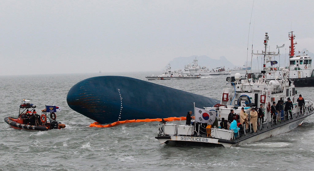 . South Korean Coast Guard officers try to rescue missing passengers from a sunken ferry in the water off the southern coast near Jindo, South Korea, Thursday, April 17, 2014.  (AP Photo/Ahn Young-joon, File)