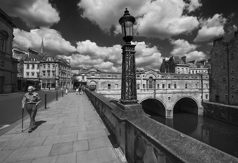Pulteney Bridge crosses the River Avon in Bath, England. It was completed by 1774, and connected the city with the land of the Pulteney family which they wished to develop. Designed by Robert Adam in a Palladian style, it is exceptional in having shops built across its full span on both sides.   Bath, England, 2018