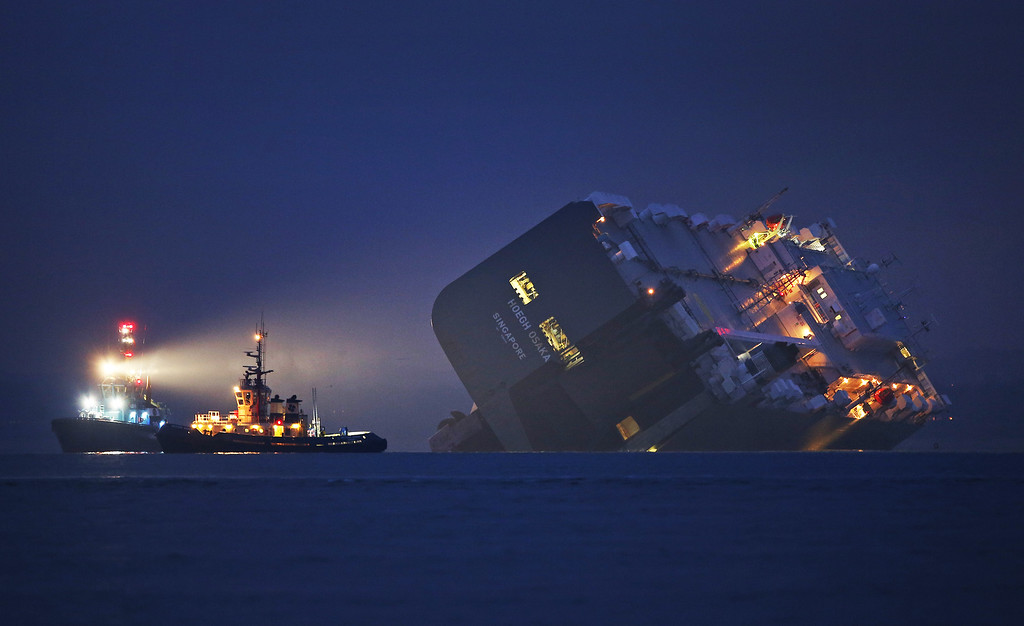 . A salvage tug lights the hull of the stricken Hoegh Osaka cargo ship after it ran aground on a sand bank in the Solent on January 4, 2015 in Cowes, England. The cargo ship ran aground on Bramble Bank after leaving Southampton bound for Germany. All 25 crew members were rescued overnight.  (Photo by Peter Macdiarmid/Getty Images)