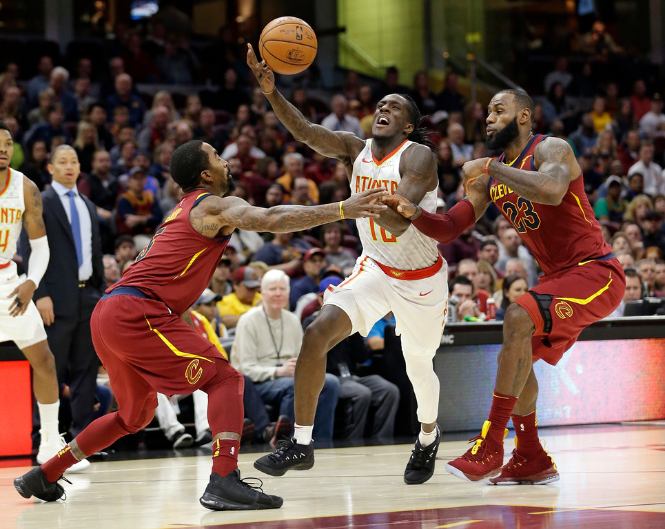. Atlanta Hawks\' Taurean Prince, center, loses control of the ball while driving between Cleveland Cavaliers\' JR Smith, left, and LeBron James, right, in the first half of an NBA basketball game, Sunday, Nov. 5, 2017, in Cleveland. (AP Photo/Tony Dejak)
