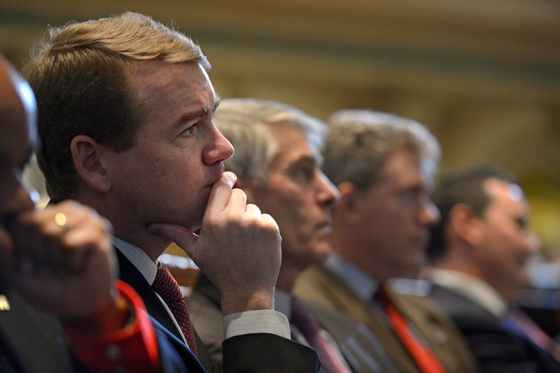 ". Colorado Senator Michael Bennet listens to the governor\'s speech. Governor John Hickenlooper gave his third State of the State address before a packed audience in the House Chambers of the State Capitol on January 10th, 2013.  The Governor took on the issue of gun regulations in his State of the State speech  calling for universal background checks for all gun purchases. In his third such address to the legislature, Hickenlooper, a Democrat, also called for a moment of silence in the House chamber to remember the victims of the Aurora shooting massacre and said Coloradans ""have an obligation to prevent similar tragedies.\"" The mayor, police chief and fire chief of Aurora were present for the governor\'s annual address.  -  Helen H. Richardson, The Denver Post"