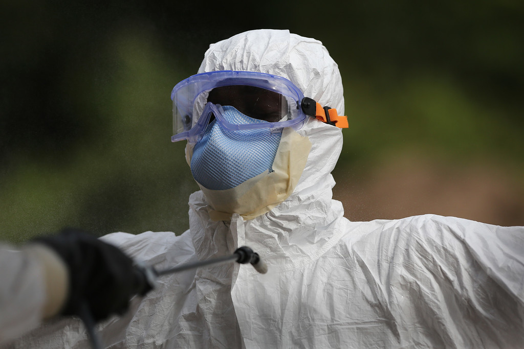 ". A burial team member wearing personal protective equipment (PPE), stands for decontamination spray at the U.S.-built cemetery for ""safe burials\"" on January 27, 2015 in Disco Hill, Liberia.   (Photo by John Moore/Getty Images)"