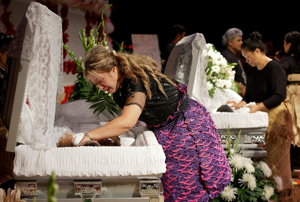 ". Poliana Taufa, front, the biological mother of Texas A&M redshirt freshman Polo Manukainiu, weeps as she leans over his casket during a memorial service for Manukainiu and his brother Andrew ""Lolo\"" Uhatafe, rear, Friday, Aug. 9, 2013, in Euless, Texas. The two were killed in a single car accident in New Mexico, on July 29. Also killed was 18-year-old Utah recruit Gaius \""Keio\"" Vaenuku. (AP Photo/Tony Gutierrez)"