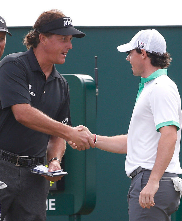 . Phil Mickelson of the United States, left, and Rory McIlroy of Northern Ireland shake hands on the first hole during the first round of the British Open Golf Championship at Muirfield, Scotland, Thursday July 18, 2013. (AP Photo/Peter Morrison)