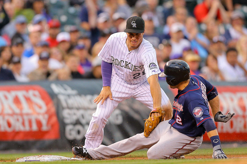 . DENVER, CO - JULY 11: Nolan Arenado #28 of the Colorado Rockies applies the tag as Brian Dozier #2 of the Minnesota Twins is caught advancing to third on a throw from right fielder Carlos Gonzalez (not pictured) of the Colorado Rockies during the third inning at Coors Field on July 11, 2014 in Denver, Colorado. (Photo by Justin Edmonds/Getty Images)